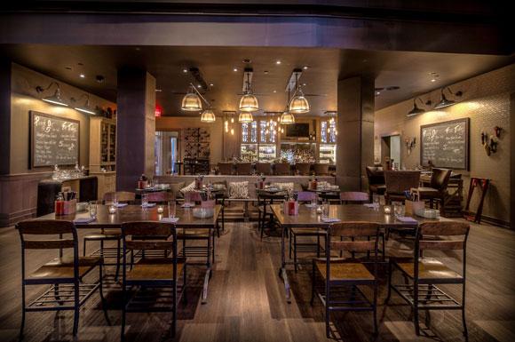 American walnut flooring and subtle lighting create a moody speakeasy-like atmosphere.