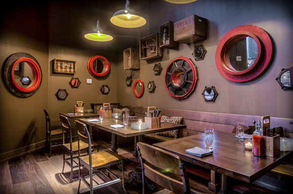 The walls feature vintage beverage crates from local Atlanta companies such as Atlas Beverages, while old metal gears and wooden foundry molds frame mirrors.