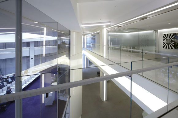 The expanded slab opening creates a visual connection between floors, illuminated by custom Zomtobel light fixtures.